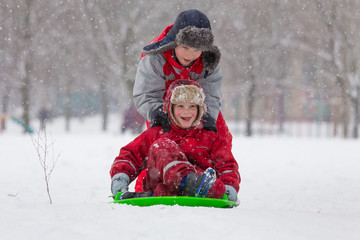 Two boys riding at the slide on snowy landscape