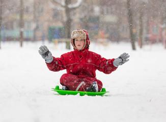 Adorable boy sitting at slide on snowy landscape