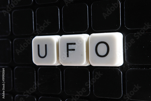 Canvas UFO UFO text word title caption label cover backdrop background. Alphabet letter toy blocks on black reflective background. White alphabetical letters. White educational toy block with words