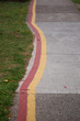 PAINT LINES ON A SIDEWALK FOLLOWING THE CURVE OF THE OVERGROWN LANDSCAPING