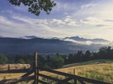Blick über Wiesen und Berge mit einem Holzzaun im Vordergrund