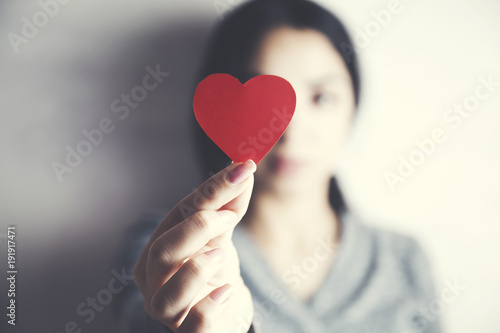 woman hand red heart in face