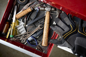 overhead view of toolbox full of tools and work gloves inside a workshop.