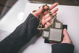Woman holding fashionable necklace in hands. viewers perspective