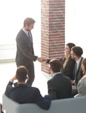 Image of business people handshaking on background of their coll
