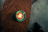 Turquoise mug of flat white coffee with heart shaped latte art on wooden table at the hipster coffee shop.  Vintage color filter effect. Flat lay, copyspace  - 191946851