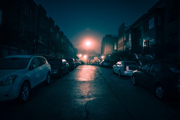 Dark wet city street with cars at night with fog. © Bruno Passigatti