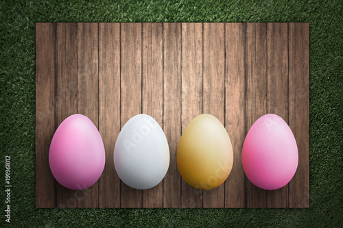 Row of Easter eggs on wooden plank