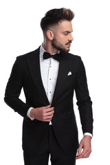 young man in tuxedo holds collar and looks to side