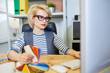 Portrait of modern blonde woman using computer at desk while working on graphic design in printing shop or publishing company, copy space