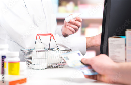 In de dag Apotheek Pharmacist and customer at pharmacy counter. Patient buying medicine and giving money. Druggist and cashier using cash register. Pill bottles in shopping basket in drug store. Medical prices and cost.