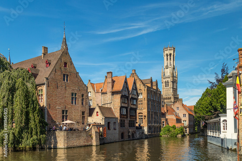 Fotobehang Brugge The Rozenhoedkaai canal in Bruges with the belfry in the background. Typical view of Bruges (Brugge), Belgium with red brick houses with triangle shaped roofs and canals.