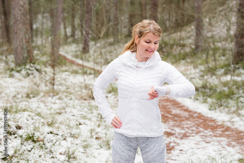 Woman looking at her watch during training outdoors in winter