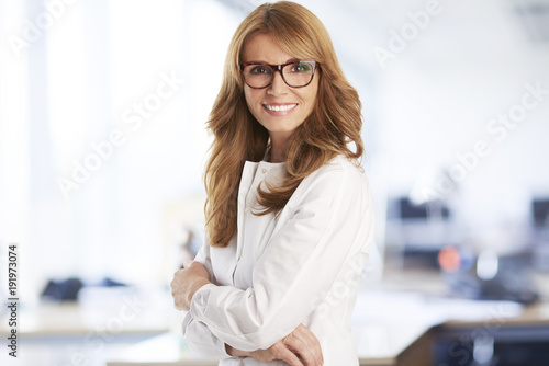 Fototapeta Lab testing. An executive middle aged medical assistant woman holding a test cube in her hand and preparing for medical lab test while sitting in front of microscope.
