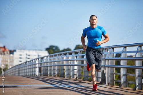 Fotobehang Hardlopen Handsome athletic man out jogging in the city