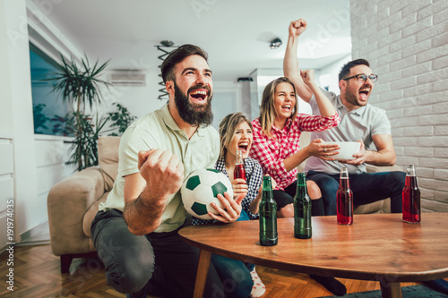 Fotobehang Voetbal Happy friends or football fans watching soccer on tv and celebrating victory at home.Friendship, sports and entertainment concept.