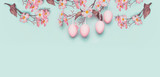 Easter banner with hanging pastel pink Easter eggs and spring blossom at light at blue turquoise background. Copy space - 191974614