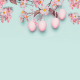 Easter layout with hanging pastel pink eggs and spring blossom at light at blue turquoise background. Copy space for greeting or invitation - 191974654