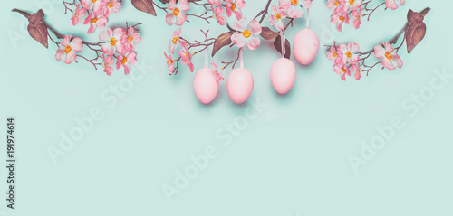 Easter banner with hanging pastel pink Easter eggs and spring blossom at light at blue turquoise background. Copy space