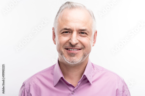 Refined maturity. The portrait of a handsome grey-haired bristled man in a lilac shirt smiling at the camera while posing isolated on a white background
