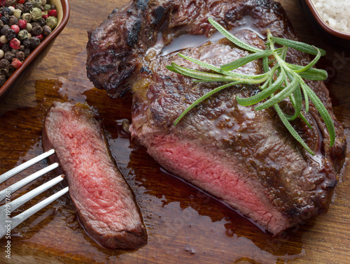 Foto op Aluminium Steakhouse medium roast steak with seasoning on wooden background