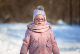 Adorable girl in winter jacket running on the snow - 191990013