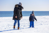 Mother with little son walking on snowy beach, Poland - 191990095