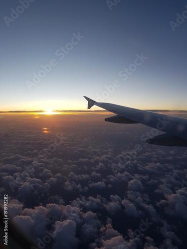 Foto Murales Coucher de soleil vu d'avion : au dessus des nuages vertical