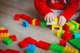 little baby playing with colorful plastic blocks