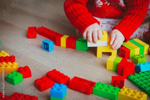 Zobacz obraz little baby playing with colorful plastic blocks