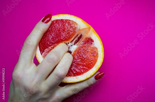Vagina symbol. Two fingers on grapefruit on pink background. Sex concept. - 191998252