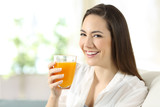 Woman holding a glass of orange juice at home - 192005892