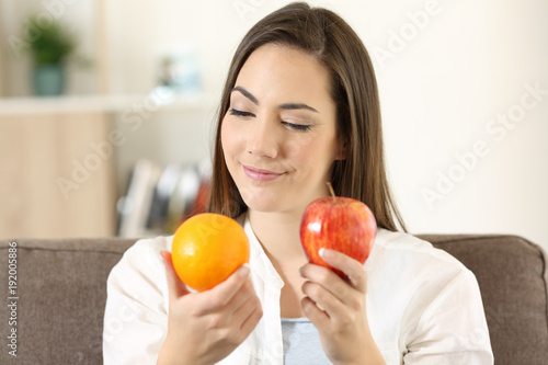 Woman deciding between an orange and apple