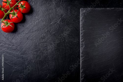 Fresh cherry tomatoes on a black background with slate plate. Top view with copy space. - 192006673