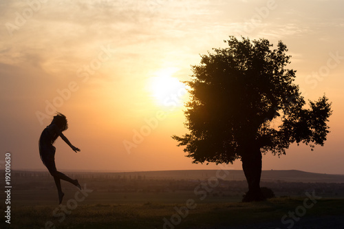 Silhouette of a beautiful young girl jumping in the sunset light near a tree