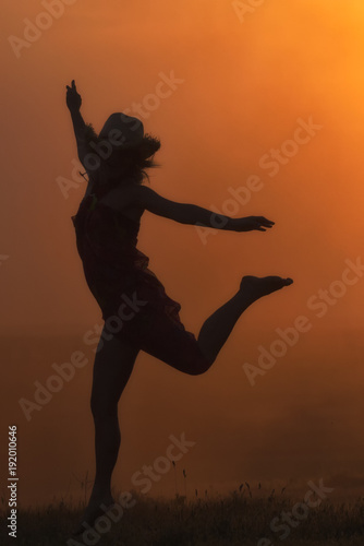 Silhouette of a beautiful young girl jumping in the sunset light