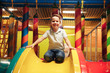 Happy little boy sitting on a slide - 192014682