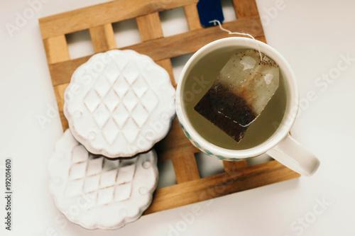 Mug with boiling water, tea bag and cookies