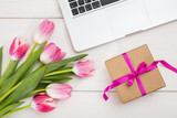 Women's day. Pink tulips, laptop and a gift on an white desk, top view