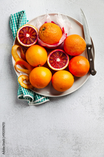 A group of oranges on a plate. some of them cut. knife and towel. on a stone background. a healthy summer table, the preparation of freshly squeezed juice or dessert, copy space
