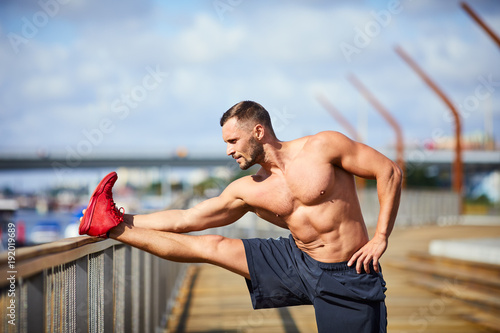 Well-built man stretching before and outdoors workout