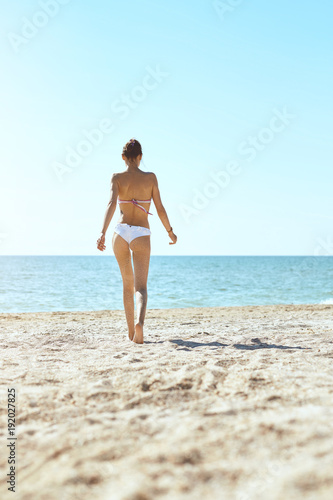Aluminium Lichtblauw beautiful sexual young woman stands on the beach against the sea and sky. happy woman enjoys summer vacation and goes to swim in the sea