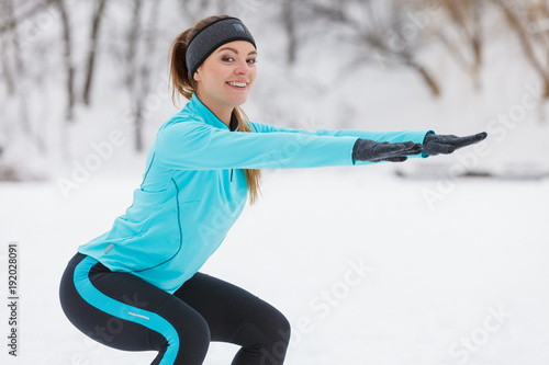 Winter workout. Girl wearing sportswear doing squats