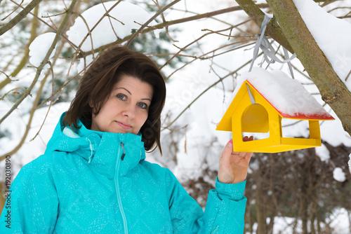 Woman stands near yellow bird feeder