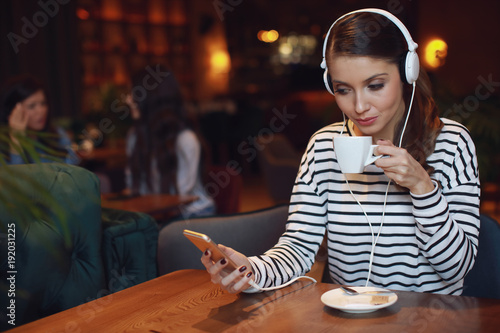 Young woman listening to music via headphones drink coffee in a cafe