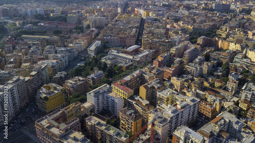Aerial view of a group of buildings in the Tuscolana district in Rome, city e capital of Italy. The roofs are passable and with antennas and TV. down the sun lit streets there are cars and trees.