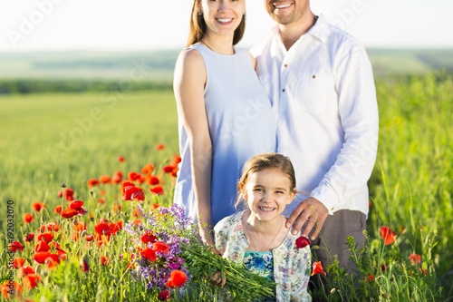Portrait of a young big pregnant family in poppy field