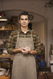 Handsome young man in pottery workshop holding clay - 192033810