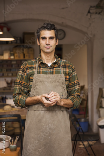Handsome young man in pottery workshop holding clay