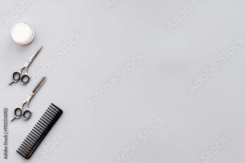 Fototapeta Professional hairdressing tools in beauty saloon. Combs, sciccors on grey background top view copy space
